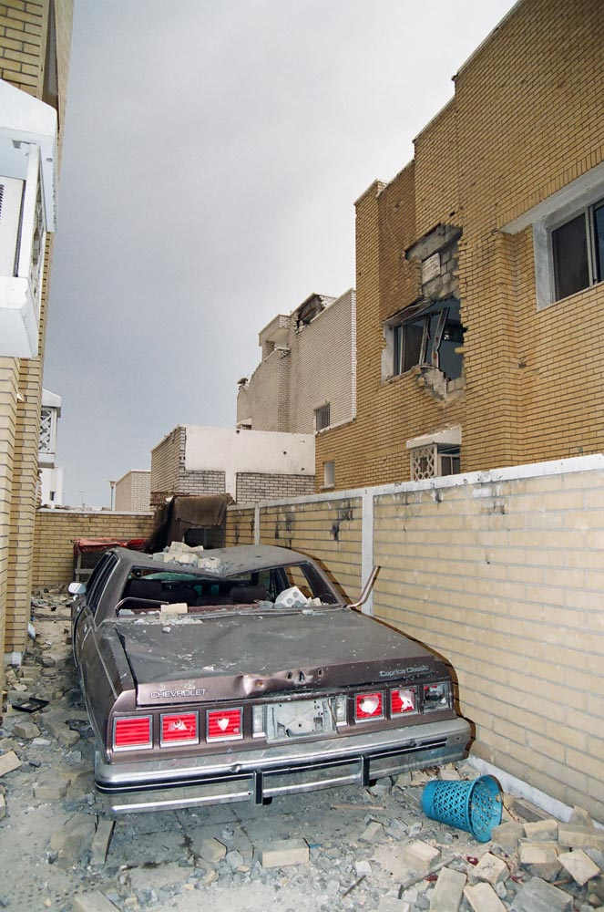 Al-Qurain House Exterior in 1991  The car of the homeowner and martyr, Bader Nasser Eidan, was caught in the crossfire of the battle. (See also Overview page 7 and Overview page 9 and .)
